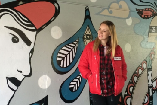 Artist Ola Volo standing in front of her mural West Coast Folklore